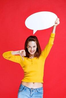 Młoda kobieta w żółtej koszuli trzyma owalną tablicę informacyjną i pokazuje kciuk w dół
