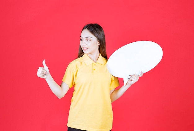 Młoda kobieta w żółtej koszuli trzyma owalną tablicę informacyjną i pokazuje pozytywny znak ręki