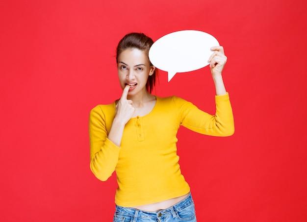 Młoda kobieta w żółtej koszuli trzyma owalną tablicę informacyjną i wygląda na zdezorientowaną i zamyśloną