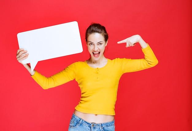 Młoda kobieta w żółtej koszuli trzyma prostokątną tablicę informacyjną
