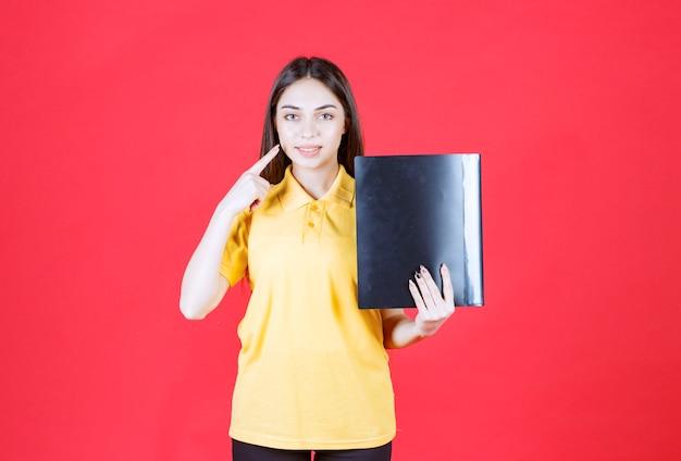 Młoda kobieta w żółtej koszuli trzymająca czarną teczkę