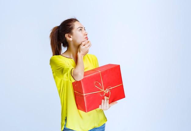 Młoda kobieta w żółtej koszuli trzymająca czerwone pudełko i myśląca lub wahająca się