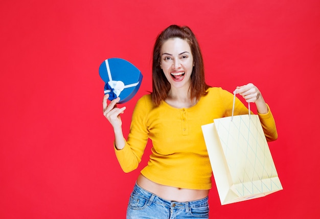 Młoda kobieta w żółtej koszuli trzymająca kartonową torbę na zakupy, zabierająca tam niebieskie pudełko i czując się zaskoczona