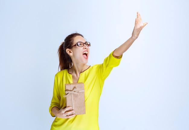 Młoda kobieta w żółtej koszuli trzymająca kartonowe pudełko i zapraszająca osobę do wręczenia go