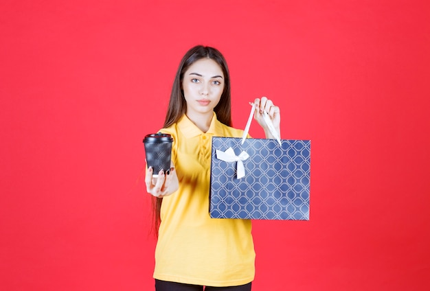 Młoda kobieta w żółtej koszuli trzymająca niebieską torbę na zakupy i czarną jednorazową filiżankę napoju