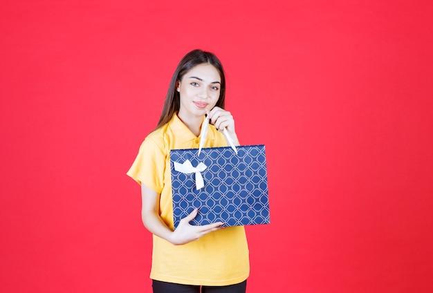 Młoda kobieta w żółtej koszuli trzymająca niebieską torbę na zakupy