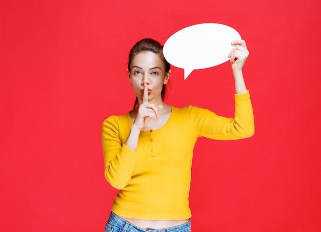 Młoda kobieta w żółtej koszuli trzymająca owalną tablicę informacyjną i proszącą o ciszę