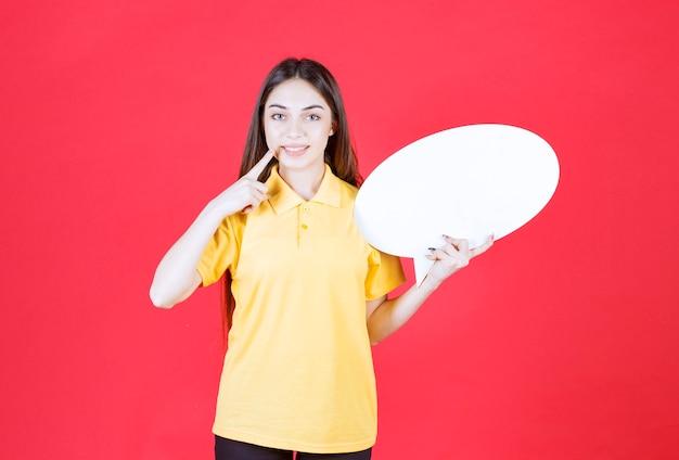 Młoda kobieta w żółtej koszuli trzymająca owalną tablicę informacyjną