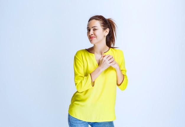 Młoda kobieta w żółtej koszuli, wskazując na siebie