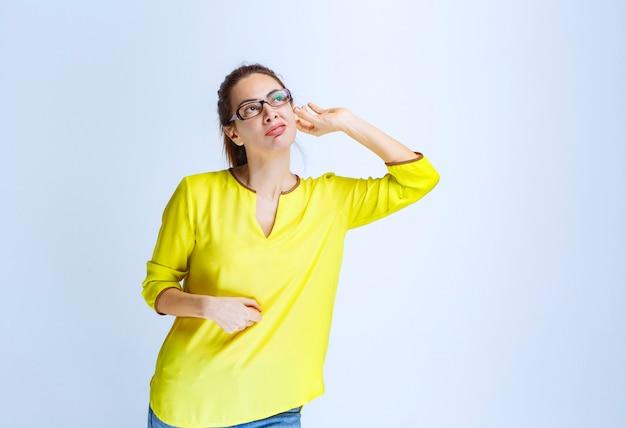 Młoda kobieta w żółtej koszuli wygląda na zamyśloną