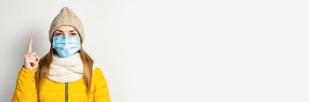 Młoda kobieta w żółtej kurtce i kapeluszu z maską medyczną na białym tle