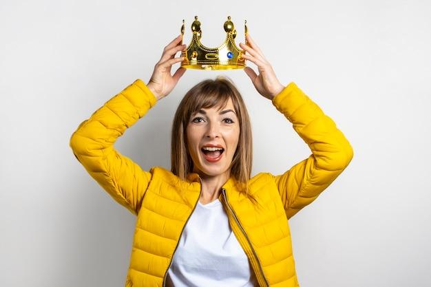 Młoda kobieta w żółtej kurtce i złotej koronie na białym tle