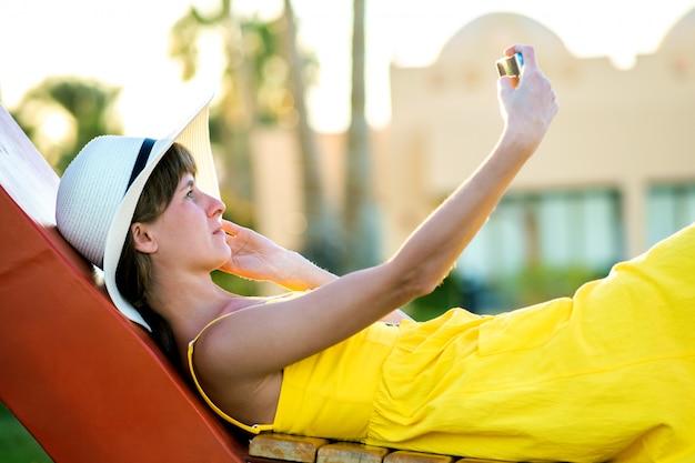 Młoda kobieta w żółtej lato sukni bierze selfie z jej telefonem komórkowym odpoczywa na ławce w parku.