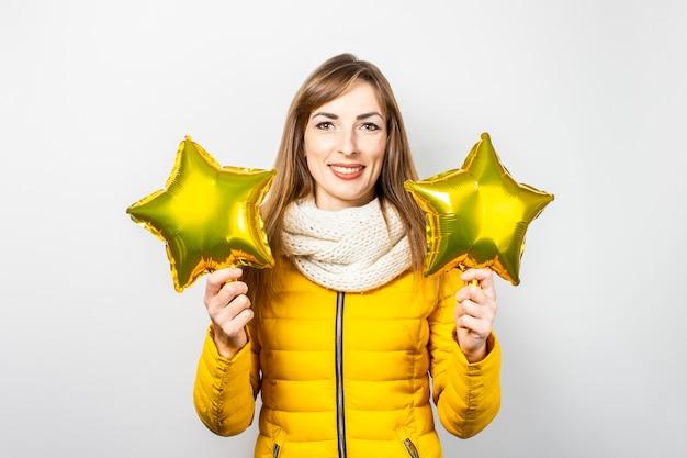 Młoda kobieta w żółtej puchowej kurtce i kapeluszu na białym tle