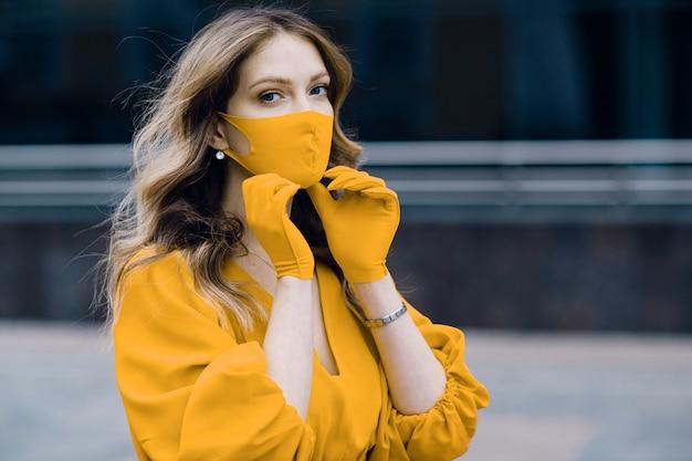 Młoda kobieta w żółtej sukience i rękawiczkach stawia na ulicy medyczną maskę ochronną. koncepcja kwarantanny koronawirusa covid-19.