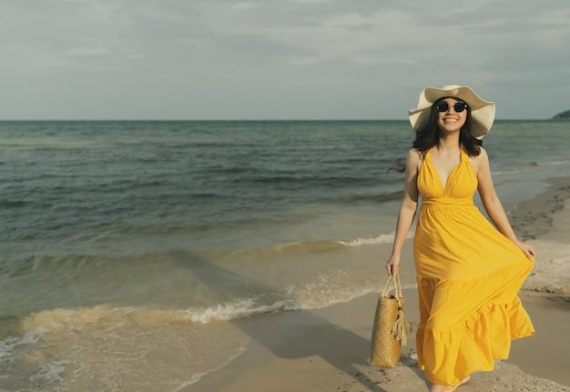 Młoda kobieta w żółtej sukience spaceru na plaży