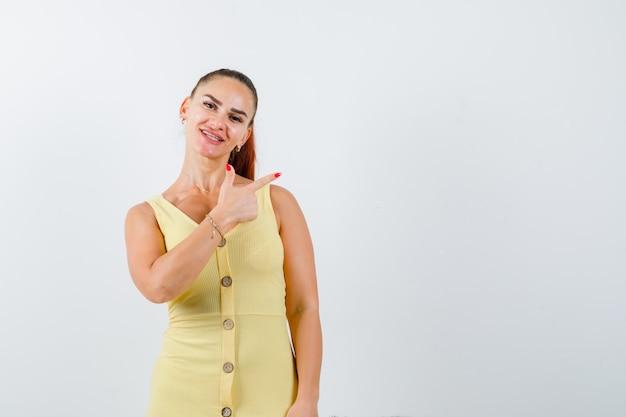 Młoda kobieta w żółtej sukience, wskazując w prawym górnym rogu i patrząc wesoło