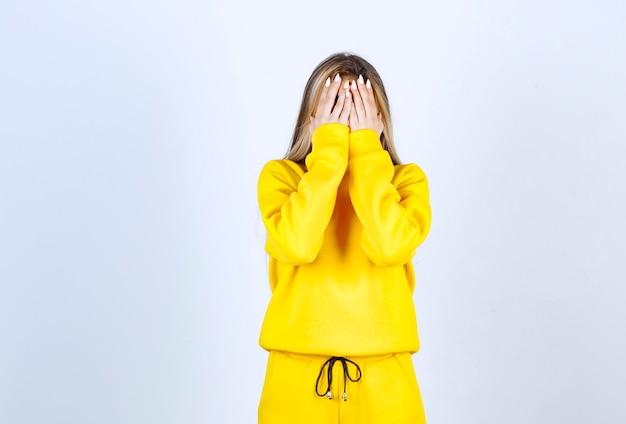 Młoda kobieta w żółtym dresie zakrywającym jej twarz na białej ścianie