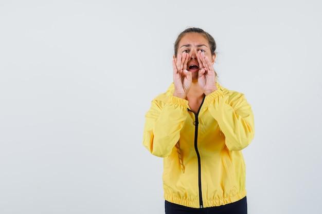 Młoda kobieta w żółtym płaszczu przeciwdeszczowym dzwoni do kogoś donośnym głosem i wygląda na skoncentrowaną