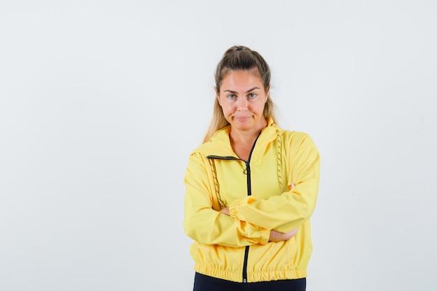 Młoda kobieta w żółtym płaszczu przeciwdeszczowym, patrząc z przodu, trzymając ręce skrzyżowane i wyglądając na niezadowolonego