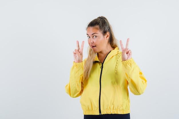 Młoda kobieta w żółtym płaszczu przeciwdeszczowym pokazuje znak v.