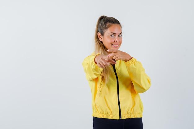 Młoda kobieta w żółtym płaszczu, wskazując na przód i patrząc radośnie