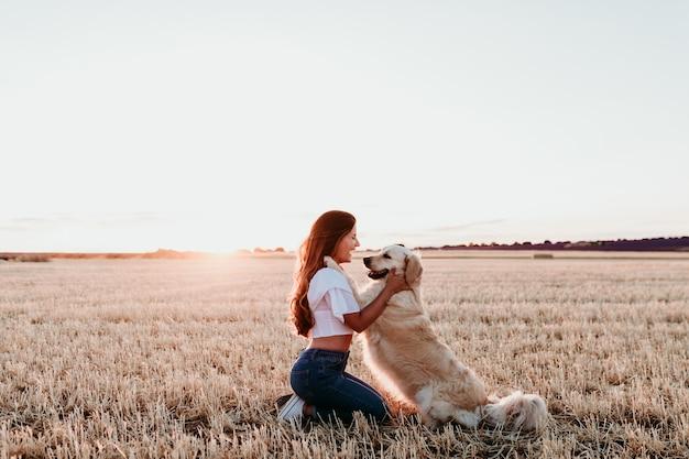 Młoda kobieta w żółtym polu z jej golden retriever psem przy zmierzchem. zwierzęta na zewnątrz