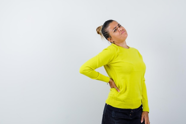 Młoda kobieta w żółtym swetrze i czarnych spodniach trzyma rękę za talią i wygląda na zmęczoną