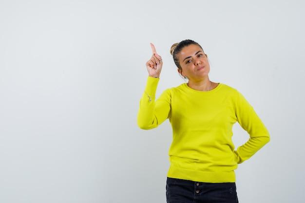 Młoda kobieta w żółtym swetrze i czarnych spodniach, wskazująca w górę i trzymająca rękę w talii, wygląda na szczęśliwą