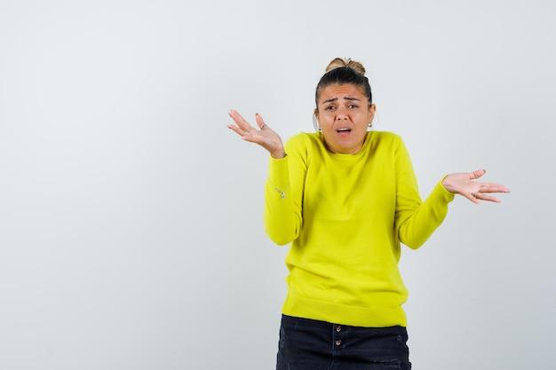 Młoda kobieta w żółtym swetrze i czarnych spodniach wyciąga dłonie pytająco i wygląda na zdziwioną