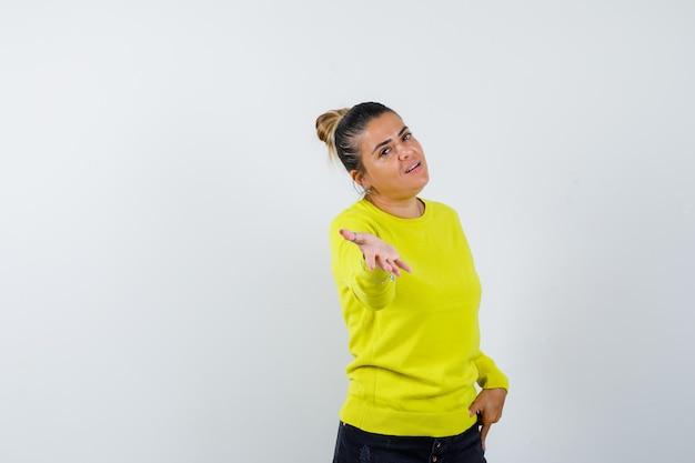 Młoda kobieta w żółtym swetrze i czarnych spodniach wyciąga rękę w kierunku aparatu i wygląda na szczęśliwą