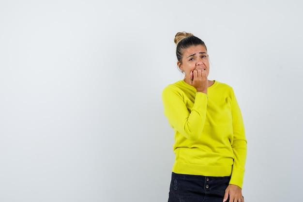 Młoda kobieta w żółtym swetrze i czarnych spodniach zakrywających usta dłonią, gryząca pięść i wyglądająca na zmęczoną