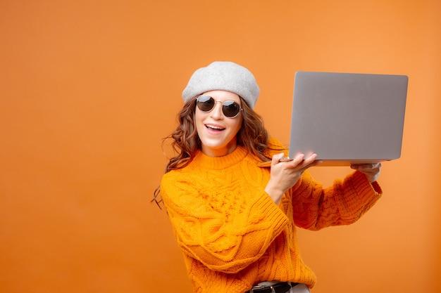 Młoda kobieta w żółtym swetrze na żółtym tle trzyma laptopa