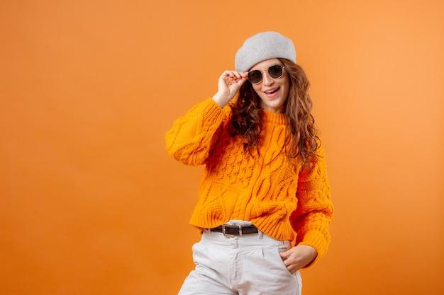 Młoda kobieta w żółtym swetrze na żółtym tle
