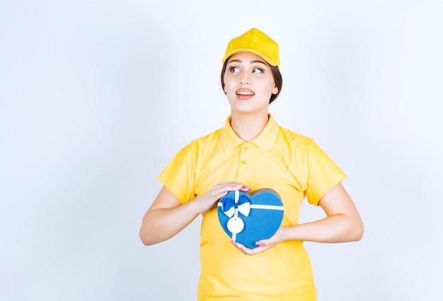 Młoda kobieta w żółtym unishape trzymająca pudełko w kształcie serca