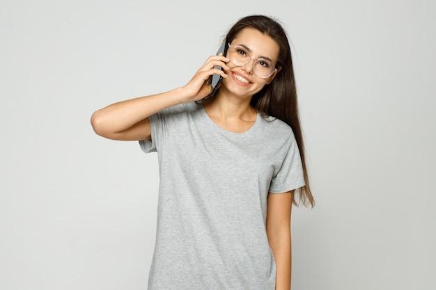 Młoda kobieta w zwykłych ubraniach i okularach rozmawia na smartfonie i wyraża szczęście