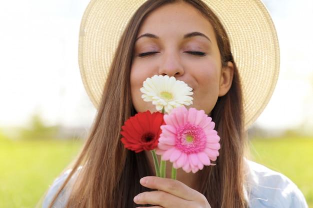 Młoda kobieta wącha kwiaty gerbera