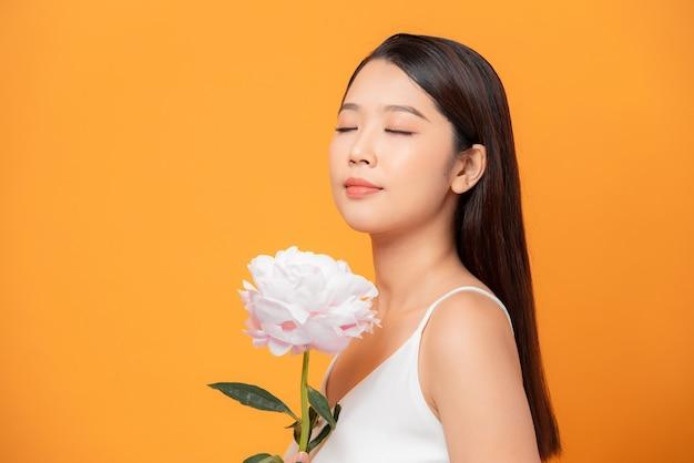 Młoda kobieta wąchająca różowy kwiat piwonii zamknęła oczy na żółtym tle