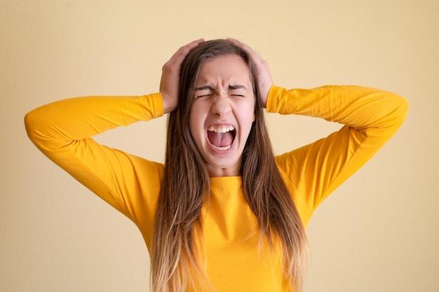 Młoda kobieta wariuje na żółtym tle
