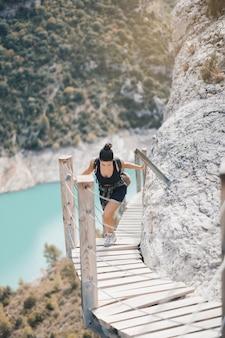 Młoda kobieta wędruje po wiszących schodach
