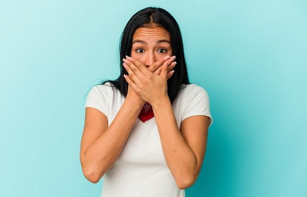 Młoda kobieta wenezuelska na białym tle na niebieskiej ścianie obejmujące usta rękami patrząc zmartwiony.