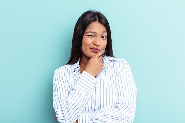 Młoda kobieta wenezuelska na białym tle na niebieskim tle patrząc w bok z wyrazem wątpliwości i sceptyczny.