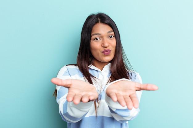 Młoda kobieta wenezuelska na białym tle na niebieskim tle składane usta i trzymając dłonie, aby wysłać pocałunek powietrza.