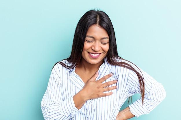 Młoda kobieta wenezuelska na białym tle na niebieskim tle śmiejąc się trzymając ręce na sercu, pojęcie szczęścia.