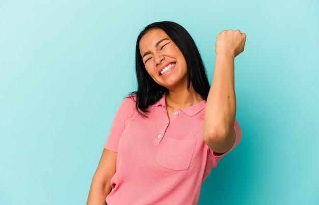 Młoda kobieta wenezuelska na białym tle na niebieskim tle świętuje zwycięstwo, pasję i entuzjazm, szczęśliwy wyraz.