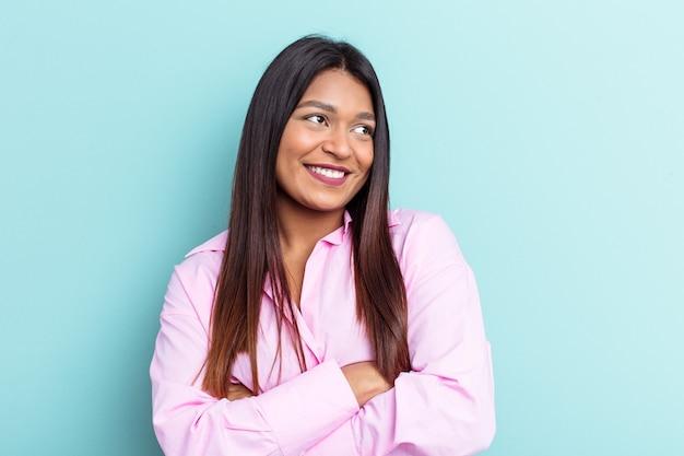 Młoda kobieta wenezuelska na białym tle na niebieskim tle uśmiechający się pewnie ze skrzyżowanymi rękami.