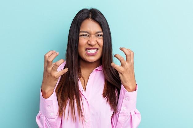 Młoda kobieta wenezuelska na białym tle na niebieskim tle zdenerwowany krzykiem z napiętymi rękami.
