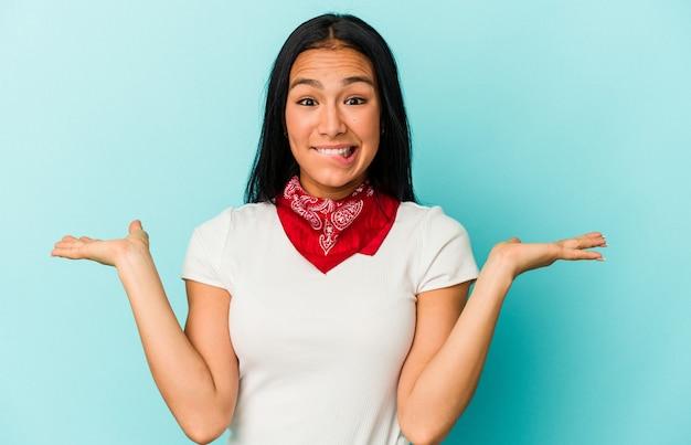 Młoda kobieta wenezuelska na białym tle na niebieskim tle zdezorientowana i wątpliwa wzruszając ramionami, aby trzymać miejsce na kopię.