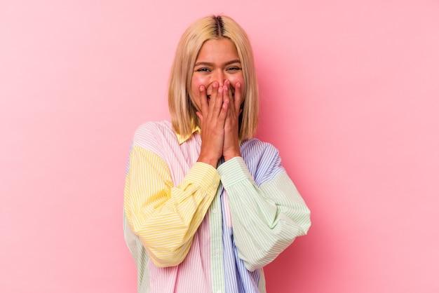 Młoda kobieta wenezuelska na białym tle na różowym tle śmiejąc się z czegoś, zakrywając usta rękami.