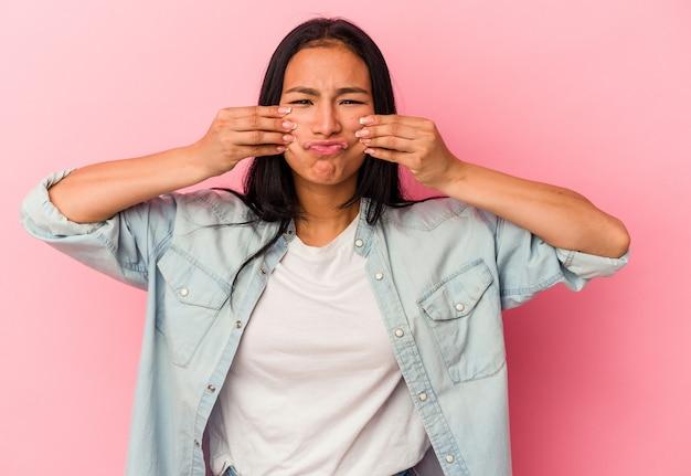 Młoda kobieta wenezuelska na białym tle na różowym tle wątpi między dwiema opcjami.